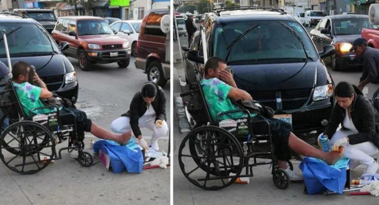 Enfermeira ajoelha-se em calçada para tratar feridas de morador de rua
